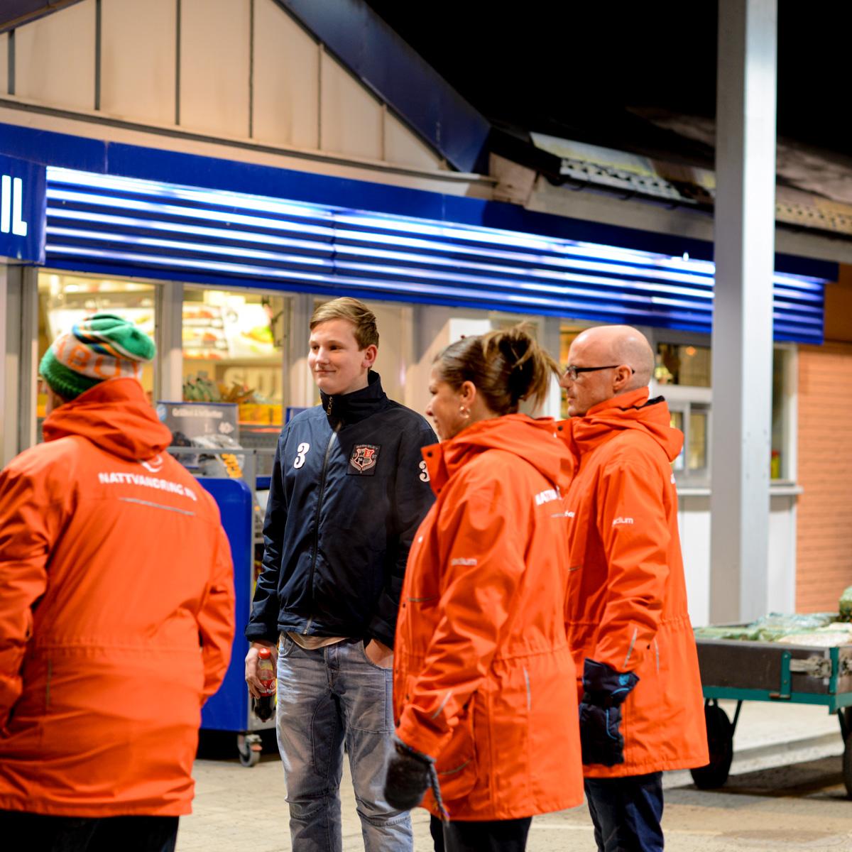 En grupp nattvandrare pratar med en ungdom.